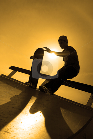 Skateboarder Silhouette stock photo, A silhouette of a young skateboarder at the top of a ramp at the skate park. by Todd Arena