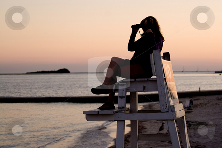 Lifeguard with Binoculars stock photo, A silhouette of a woman looking with binoculars at the beach while seated in a lifeguard chair. by Todd Arena