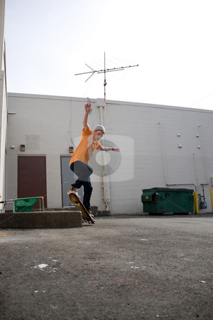 Skateboarder Grinding stock photo, Portrait of a young skateboarder performing a trick in an urban setting. by Todd Arena