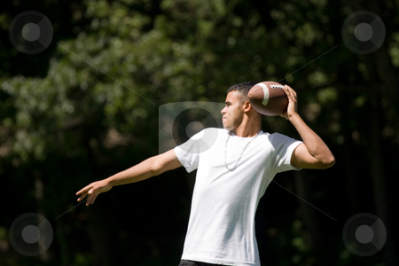 Tossing the Fooball stock photo, A young adult throwing a football outside. by Todd Arena