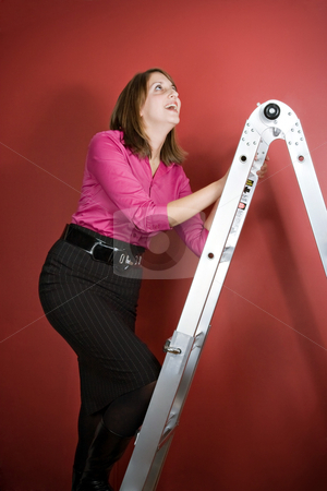 Climbing the Ladder stock photo, A young woman climbs a ladder over a red background. by Todd Arena