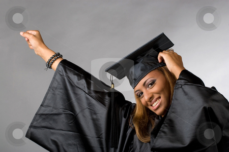 Happy Graduate  stock photo, A recent graduate posing in her cap and gown isolated over a silver background. by Todd Arena