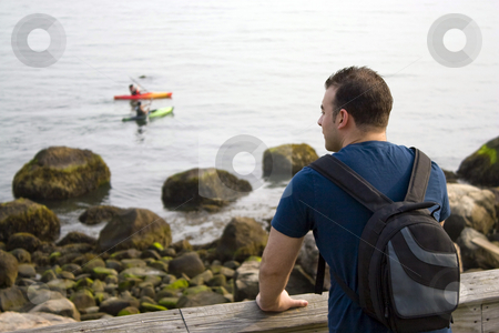 The Ocean View stock photo, A young man enjoys the view by the sea as two people kayak in the distance.  Shallow depth of field. by Todd Arena