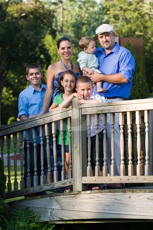 Family Portrait stock photo, Portrait of an attractive young family with four children posing in a park on a wooden walking bridge. by Todd Arena