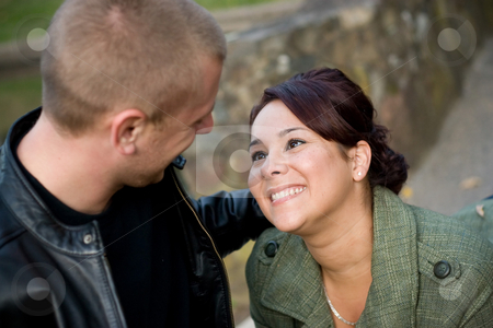 Young Couple Dating stock photo, A young happy couple looking fondly at one another outdoors.  Shallow depth of filed with focus in the woman. by Todd Arena