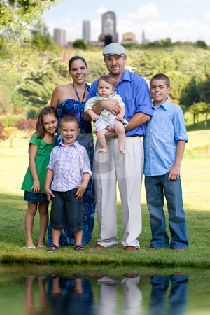 Family Portrait stock photo, Portrait of an attractive young family with four children posing in a park outside of the city. by Todd Arena
