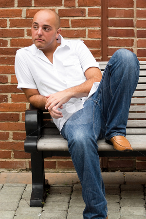 Casual Guy stock photo, A man in his twenties sitting casually on a bench in an urban area. by Todd Arena