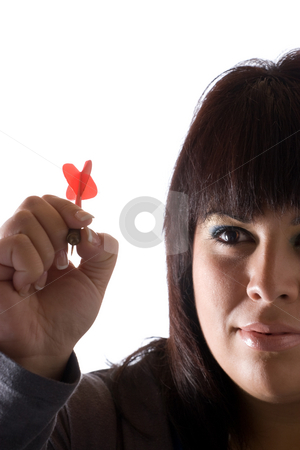 Throwing a Dart stock photo, A young woman aiming a dart as she gets ready to throw it at the target. by Todd Arena