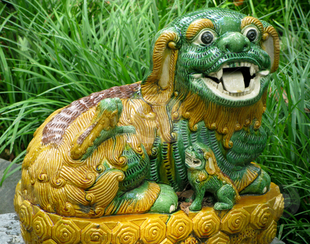 Pottery lion in grass stock photo, Close-up of pottery lion or dog in deep grass in garden by Steven Heap