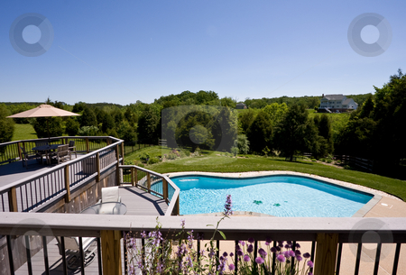Wide angle view of deck and swimming pool stock photo, Modern deck and swimming pool in expansive landscaped garden by Steven Heap