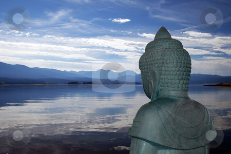 Buddha overlooking lake stock photo, Backview of Buddha statue overlooking a peaceful mountain lake by Steven Heap