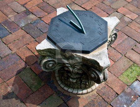 Sun dial stock photo, Close-up of sun dial on brick patio on carved stone plinth by Steven Heap