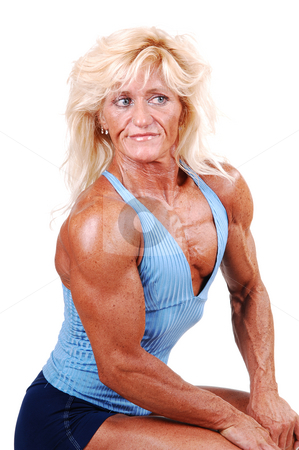 Bodybuilding woman. stock photo, A blond muscular bodybuilding girl sitting in the studio shooing her  strong legs and the upper body, over white background. by Horst Petzold