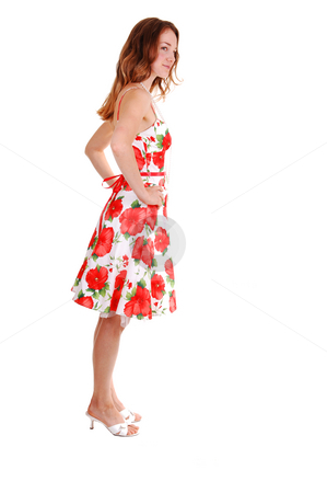 Pretty girl in colorful dress. stock photo, Young, lovely girl in a short colorful dress with brown hair,  on high heels, standing in the studio for white background. by Horst Petzold