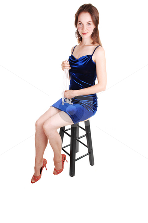Pretty girl in royal blue dress. stock photo, Young, lovely girl in a royal blue dress with brown hair, looking  in the camera,  in high heels sitting on a bar chair, in the studio for white background. by Horst Petzold