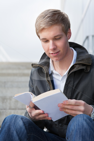Young guy with book stock photo, Young cheerful handsome guy reading a book with blank cover by Mikhail Lavrenov