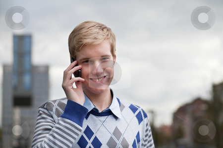 Young blond man with cellphone stock photo, Young blond man smiles while speaking outdoors on his cellphone by Mikhail Lavrenov