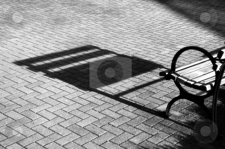 Lonely bench stock photo, The shadow of an empty bench on the bricks in the late afternoon sun by Gerry Daniel