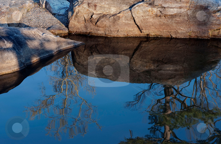 Pool reflection stock photo, The sky, trees, and rocks reflected in a pool of water by Gerry Daniel
