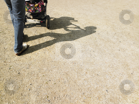 Adult Pushing Stroller stock photo, Cropped view of adult pushing a baby stroller, with shadows visible on the gorund. Horizontally framed shot. by Mog Ddl