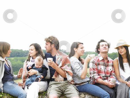 Group of People Relaxing Outdoors With Coffee stock photo, Group of young people having coffee outside in the morning, with one woman holding a baby. Horizontal. by Mog Ddl