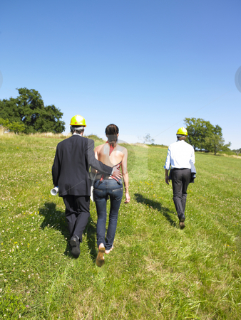 Architects Walking Outside stock photo, Group of architects walking through a meadow and wearing yellow hard hats. Horizontal. by Mog Ddl