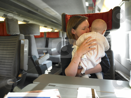 Mother Holding Baby on Train stock photo, Mother holding baby while traveling on train. Horizontally framed shot. by Mog Ddl