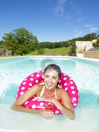 Woman Floating in Pool and Enjoying Drink stock photo, Smiling woman floating in an inner tube and drinking a beverage. Vertical by Mog Ddl
