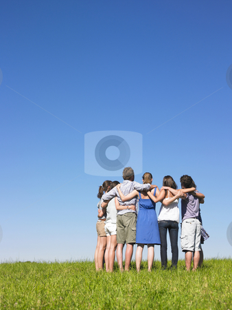 Group in semicircle stock photo, Group of friends holding sholders in meadow under blue sky by Mog Ddl