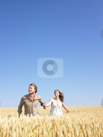 Happy Young Couple in Wheat Field stock photo, A young couple holding hands and walking through wheat field. Vertically framed shot. by Mog Ddl