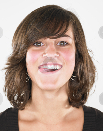Young Woman Sticking Tongue Out stock photo, Woman sticking tongue out at camera. Vertically framed shot. by Mog Ddl