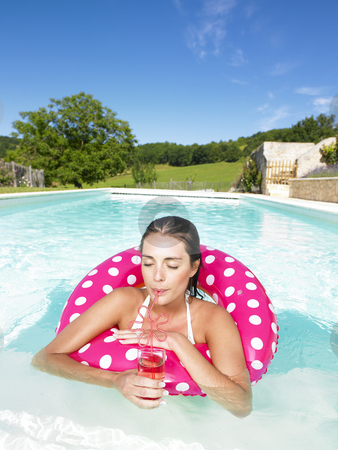 Woman Floating in Pool and Enjoying Drink stock photo, Woman floating in an inner tube and drinking a beverage with her eyes closed. Vertical by Mog Ddl