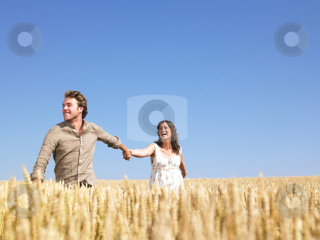 Happy Young Couple in Wheat Field stock photo, A young couple holding hands and walking through wheat field. Horizontally framed shot. by Mog Ddl