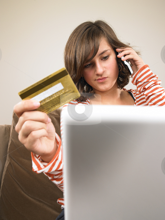 Young Woman Shopping via Phone stock photo, A young woman sits in front of a laptop, holding her credit card and talking on the phone. Vertical format. by Mog Ddl