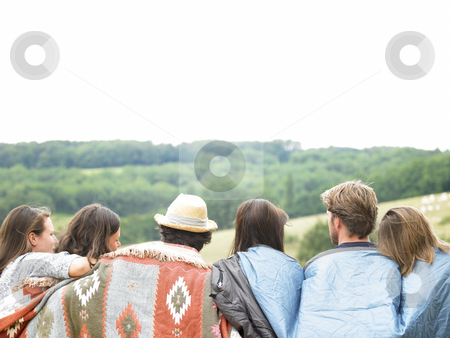 Rear View of Friends Outdoors With Blankets stock photo, Group of friends out in the country, huddled under blankets. Horizontal. by Mog Ddl