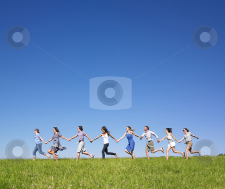 Group Holding hands running stock photo, Group of friends holding hands and running in meadow under blue sky by Mog Ddl