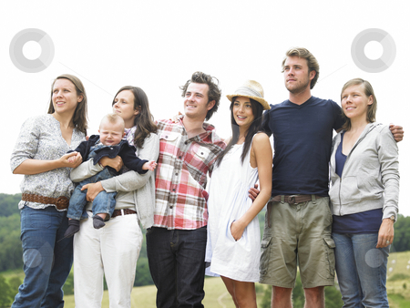 Group of Friends Standing Outdoors stock photo, Group of young people, with one woman holding a baby, standing outdoors and looking off into the distance. Horizontal. by Mog Ddl