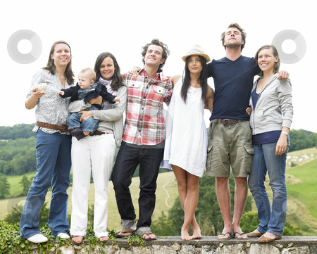 Group of Friends Standing Outdoors stock photo, Group of young people, with one woman holding a baby, standing on a stone wall outdoors. Horizontal. by Mog Ddl