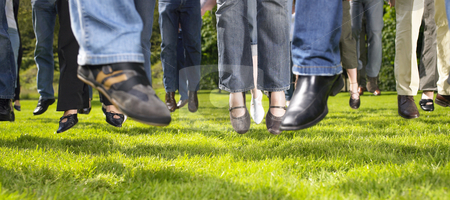 Feet Jumping on the Grass stock photo, Cropped view of group of people jumping on the grass. Horizontal. by Mog Ddl