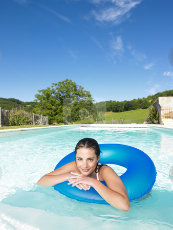 Smiling Woman Floating in Pool stock photo, Woman floating in inner tube in pool and smiling at the camera. Vertical by Mog Ddl