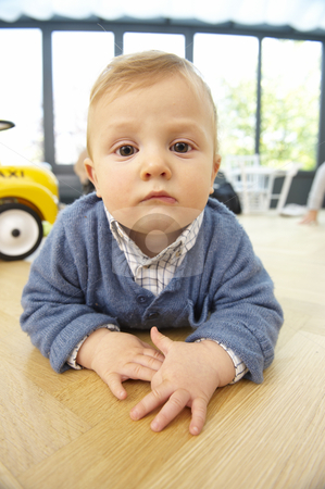 Serious Toddler Lying on the Floor stock photo, Portrait of a young boy lying on floor. Vertically framed shot. by Mog Ddl