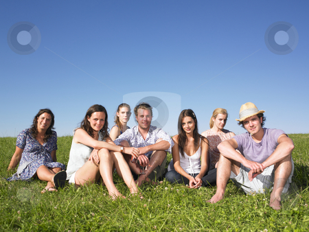 Group of People Sitting on the Grass stock photo, Seven people sitting on grass, one with hat. Horizontal. by Mog Ddl