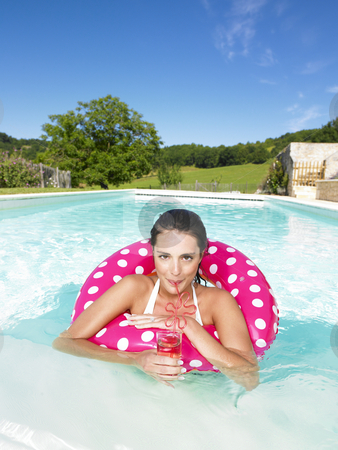Woman in pool stock photo, Woman in swimming pool having a coctail inside a pink ring by Mog Ddl
