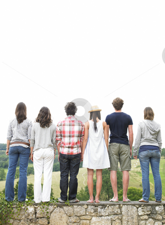 Rear View of Friends Standing on Stone Wall stock photo, Rear view of friends standing on stone wall. Vertical. by Mog Ddl
