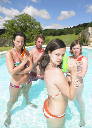 Water fight stock photo, Friends playing with water guns in pool by Mog Ddl