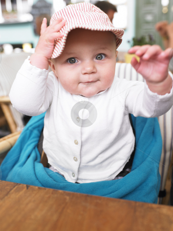 Baby at Table in Restaurant stock photo, Baby wearing a hat sits in high chair at restaurant. Vertically framed shot. by Mog Ddl