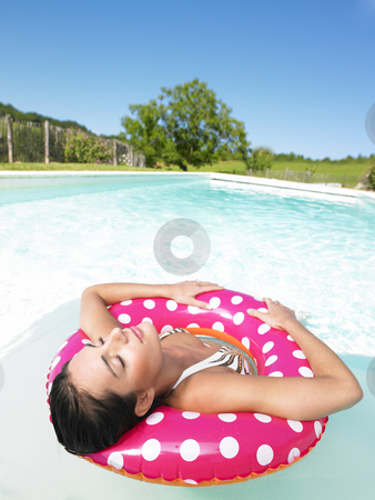Woman Floating in Pool With Eyes Closed stock photo, Woman floating in a pink polka dot inner tube with eyes closed. Vertical. by Mog Ddl