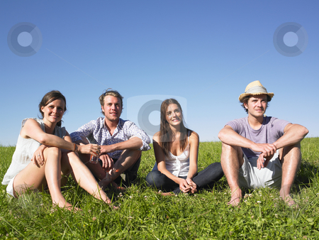 Four People Sitting on the Grass stock photo, Two men and two women sitting together on the grass. Horizontal. by Mog Ddl