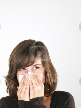 Young Woman Blowing Nose stock photo, Young woman with cold blowing nose. Vertically framed shot. by Mog Ddl
