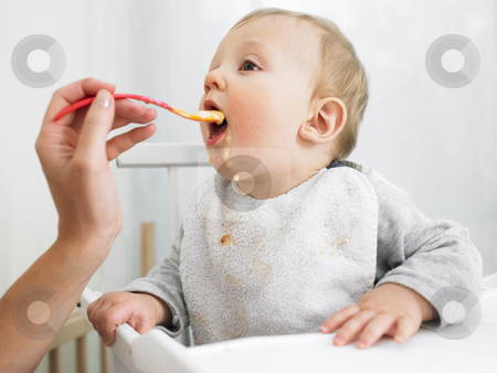 Baby Being Fed stock photo, Baby in high chair being fed by adult. Horizontally framed shot. by Mog Ddl